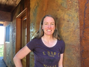 Amy Snover, director of the Climate Impacts Group at the University of Washington, stands outside her family's cabin in Pine Forest. She replaced the wood siding on the house with metal siding to improve fire resistance and participated in community tree-thinning efforts.