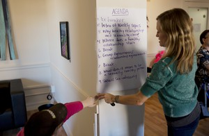 A participant helps Park hang the agenda on the wall at the start of class.