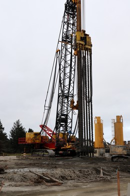 A deep-mixing drill is methodically injecting concrete underground to strengthen the subsoil under the building footprint.