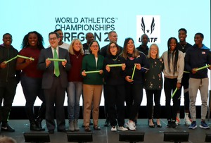 Eugene Mayor Lucy Vinis, in green sweater, and Oregon Governor Kate Brown were surrounded by medal-winning Team USA athletes at an Oregon21 kickoff rally on Thursday.