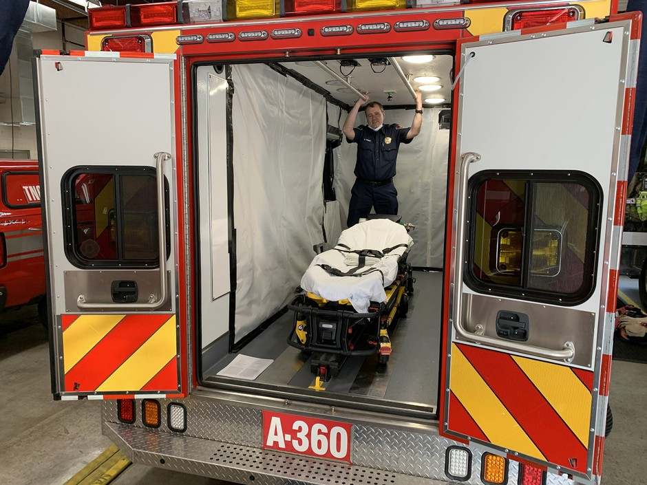 South King Fire and Rescue Lt. Greg Willett stands in an aid car optimized to transport COVID-positive patients.