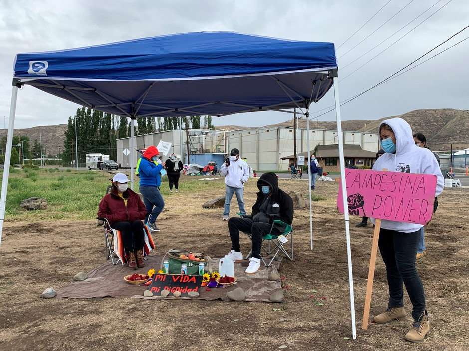 Elvira Medina and Cesar Gonzalez sit by a makeshift altar May 19 after launching a hunger strike, protesting stalled negotiations with their employer Allan Brothers Fruit and demanding a $2 dollar an hour increase in pay.