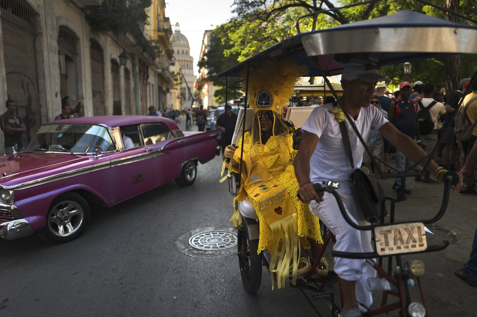 Cherice Harrison-Nelson, the Big Queen of the Mardi Gras Indians group the Guardians of the Flame, sits in traffic on a taxi bike.
