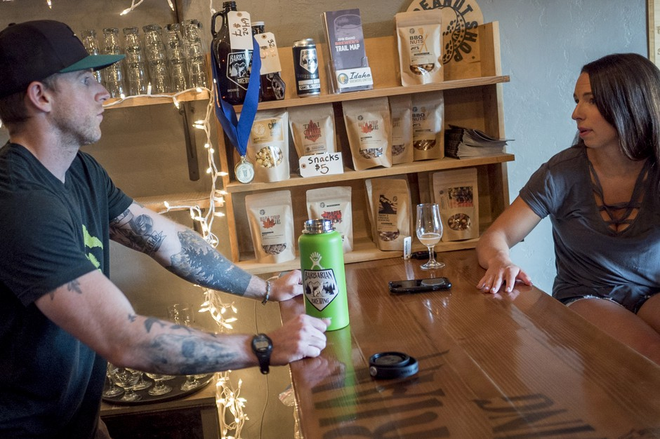 Brock Bridges, bartender at Barbarian Brewing, talks with his wife, Kayla Bridges, in the taproom. They are feeling priced out of the housing market in Boise.
