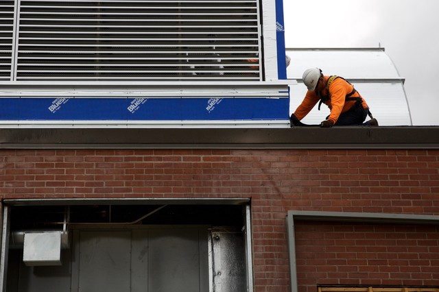 A construction worker works on the roof of Harriet Tubman Middle School.