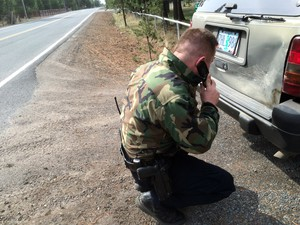 James Hayes examines the damage on a car he suspects was involved in a hit-and-run. Budget cuts in local law enforcement has led to some Fish and Wildlife troopers handling more general law enforcement.