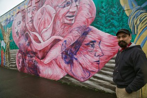 Hector Hernandez stands by his mural celebrating civil rights leaders at SE 13th and Powell Blvd.