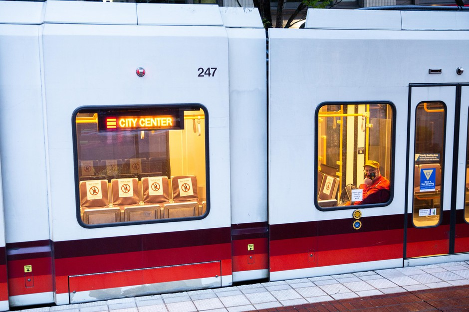 A person rides the MAX light rail Red Line train through downtown Portland, Ore., Thursday, April 29, 2020. Mass transit ridership has decreased during the COVID-19 pandemic, but many still depend on it to get around town.