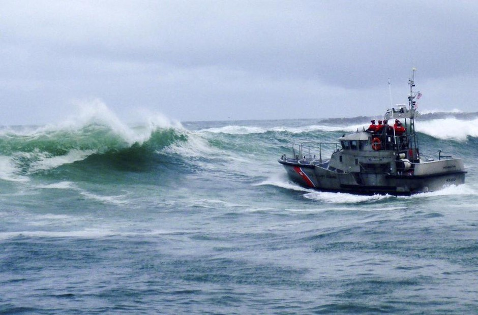 In this Tuesday, Jan. 8, 2019 photo, provided by the U.S. Coast Guard, a U.S. Coast Guard boat crew responds to three fishermen in the water aftera commercial fishing vessel capsized while crossing Yaquina Bay Bar off the coast of Newport, Ore.