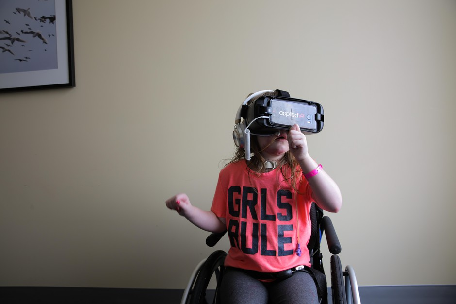 Six-year-old Moira Reeves from Baker City, Oregon, uses a virtual reality headset at the Legacy Oregon Burn Center in Portland.