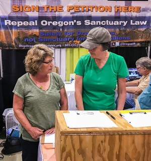 In this 2017 photo, Cynthia Kendoll, left, talks with volunteers at the Oregon State Fair booth of Oregonians for Immigration Reform. The group is gathering signatures for a proposed ballot measure that seeks to overturn the state's 30-year-old sanctuary law.