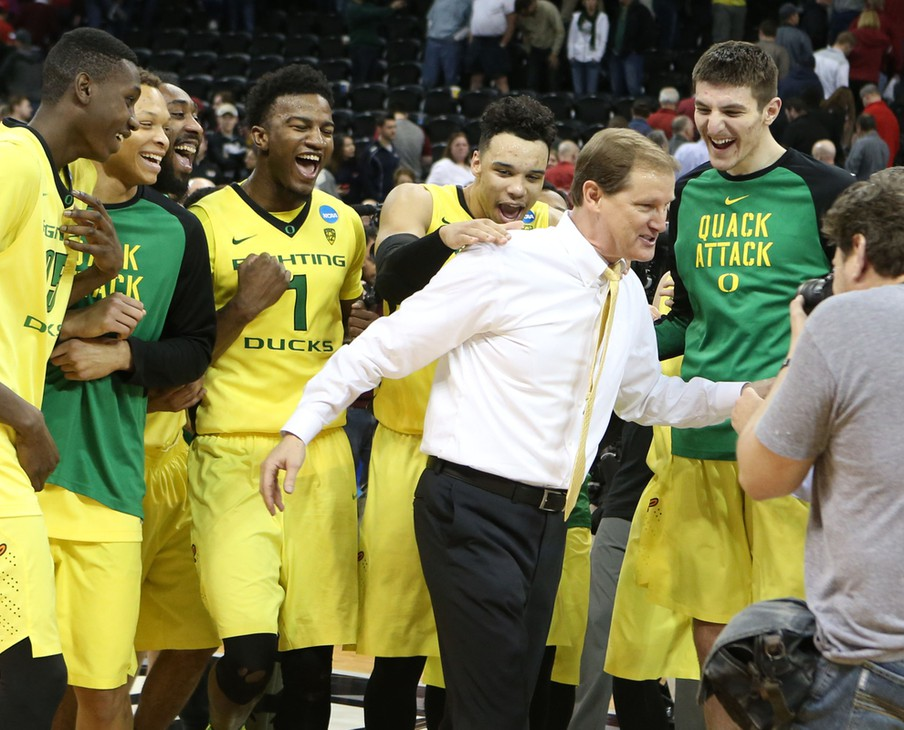 Oregon players celebrate the win over Saint Joseph's with Head Coach Dana Altman (right) after the second round of the NCAA Tournament in Spokane.