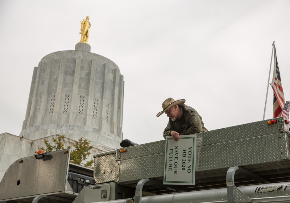 A man holding a sign in opposition to Oregon House Bill 2020 talks to fellow rallygoers from the roof of a truck at an event on the Oregon Capitol steps in Salem, Ore., on Thursday, June 27, 2019.