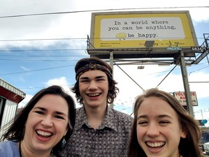 The founder of The Joy Team, Michele McKeag Larson, poses in front of a happiness billboard with her son, Kellen, and daughter, Taryn.