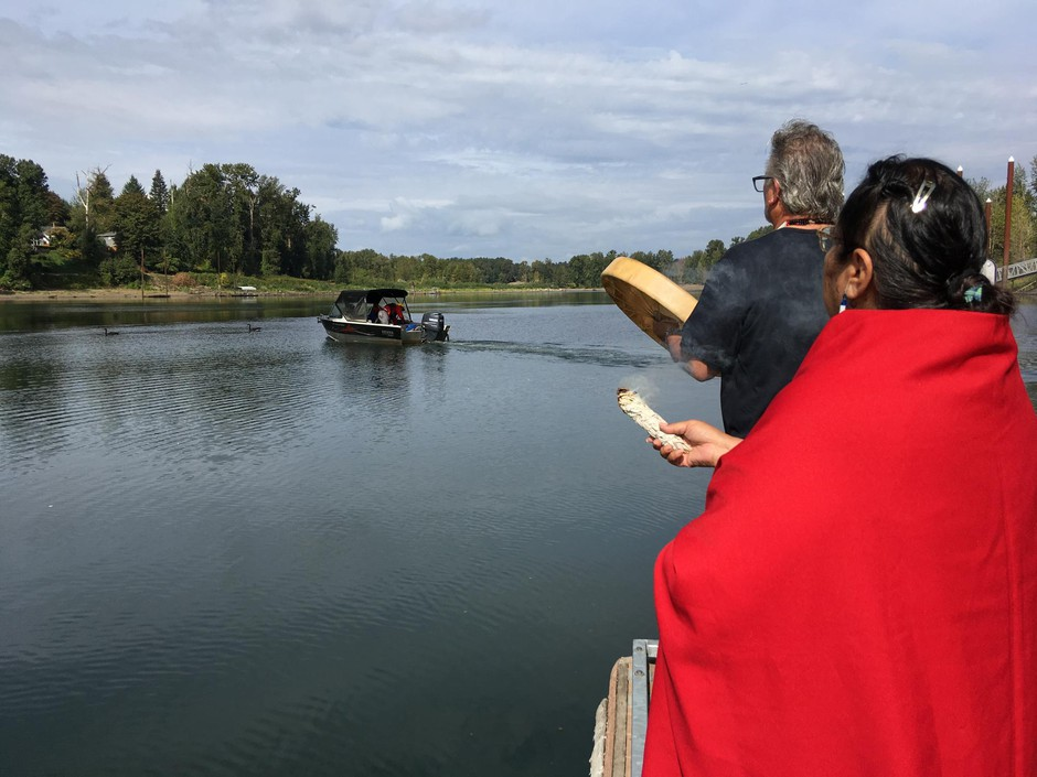 Grand Ronde Tribal Chairwoman Cheryle Kennedy and Tribal Secretary Jon A. George watch as tribal employees launch a boat to build a fishing platform at Willamette Falls.