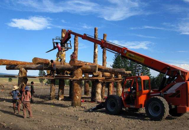 A team uses an all-terrain crane to place a log crossbeam in place on one of the structures that make up the Solar Temple.