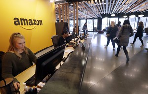 In this Nov. 13, 2018, file photo, employees walk through a lobby at Amazon's headquarters in Seattle. Many of Amazon's Seattle-area employees will likely be exempt from new proposed labor protections after a push by the tech giant's lobbyists to raise the salary threshold at which the rules would kick in.