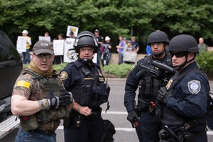 Private citizens acting as crowd control for the pro-Trump rally at Terry Schrunk Plaza Sunday, June 4, 2017, identified themselves via yellow stripes on their shoulders and backs. Law enforcement agencies have come under fire for collaborating with these citizens, some of whomare known-members of militia style groups such as the Oath Keepers and Three Percenters.