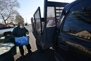 Horizon Project Inc. recycling pickup driver Dave Pauley checks a recyclingcontainer for non-recyclables while doing his morning route Tuesday, Feb. 13, 2018, in Milton-Freewater, Oregon.