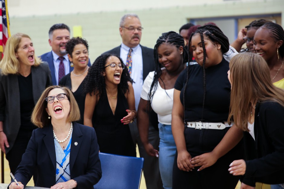 Oregon Gov.Kate Brown laughs with Jefferson High School students as she ceremonially signs the Student Success Act in Portland, Ore., Wednesday, Aug. 28, 2019.