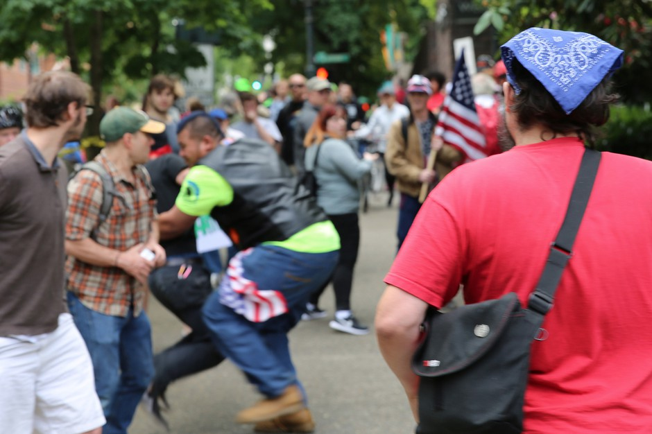 """In 2017, Tusitala """"Tiny"""" Toese, center, a known member of the militia style group, the Oath Keepers, was photographed tackling an Antifa protester before federal law enforcement officers detained the protester and arrested him."""