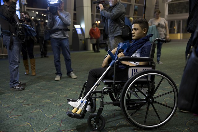 A travel weary Mustafa Abed arrives in Portland for medical attention. His leg was severed near the hip in a U.S. missile strike in Fallujah when he was two.