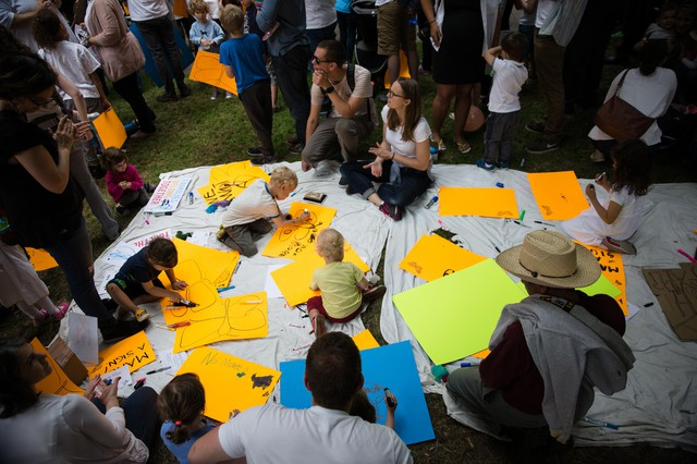 Children scribble on signs in the grass during the Families Belong Together rally in Portland.