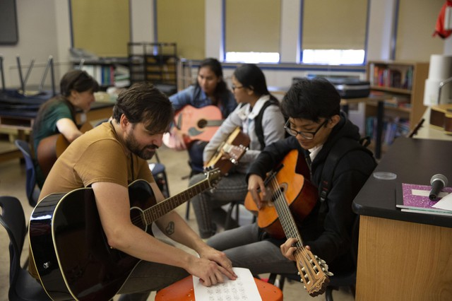 Students taking par in Pass the Mic learn from musicians about songwriting, lyrics, and cooperation.