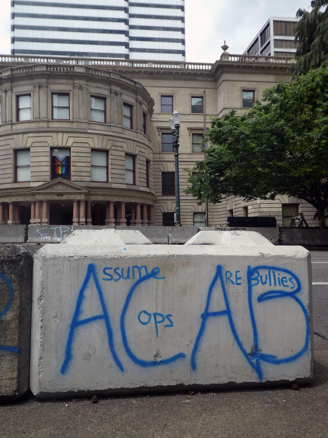 Anti-police graffiti covers barricades that line both sides of the street outside Portland City Hall. A rainbow flag inside the building's windows acknowledges June as LGBT Pride Month.