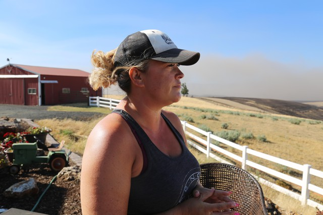 Cynthia Kortge watches the billowing wildfire smoke from her back porch in Wasco County. Her husband Jeff farms the thousands of acres of wheat on their property, most of it was destroyed in the blaze.