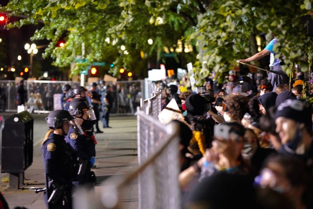 Protesters face police officers along a fence in downtown Portland on June 2, 2020.