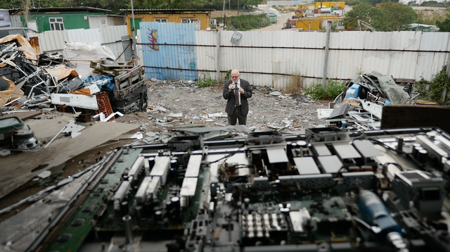 Jim Puckett, executive director of the Basel Action Network, surveys an e-waste junkyard in the New Territories region of Hong Kong. In the foreground, an LCD monitor is dismantled.