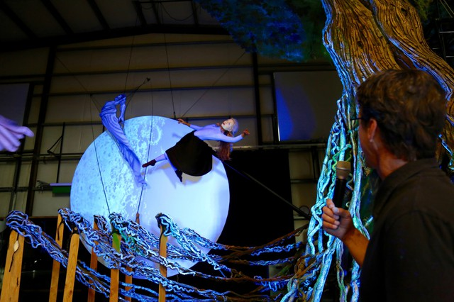 Michael Curry directs the lead actress playing Persephone in an aerial ballet scene. Thecharacter is played by both a puppet and a live actress.