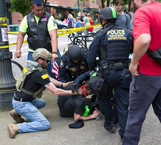 A member of the Oath Keepers helps police officers detain a protester during the dueling rallies in Portland, Oregon, June 4, 2017.