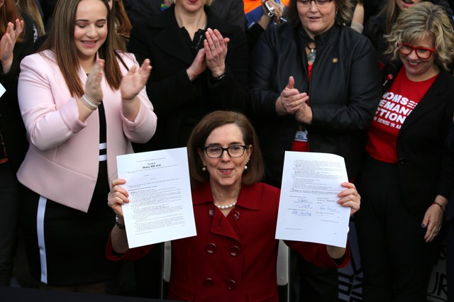 Oregon Gov. Kate Brown holds up the bill she signed into law tightening Oregon's gun laws Monday, March 5, 2018. The new law expands those excluded from owning or buying firearms or ammunition by adding people who don't live with the partner they're abusing or threatening to the list.