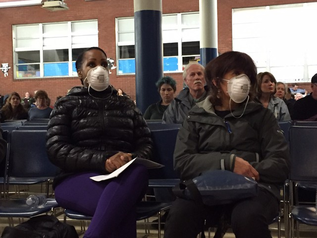 Two concerned residents wore masks to a community meeting about heavy metals detected in the air in Portland.