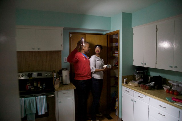 """Sara and Ed Johnson shine a flashlight in their pantry to see what they can make for their first """"Living Off Your Quake Kit"""" dinner. The Johnsons have a flashlight in each room of their house."""