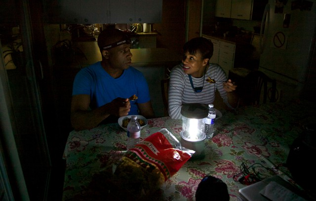The Johnsons use electric lanterns to prepare a meal in the dark at their home in Southeast Portland.