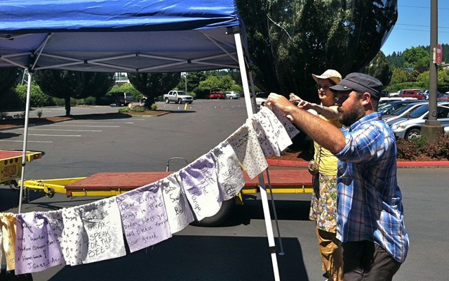 """Rozzell Medina, right, and Tanuja Goulet hang prayer flags at a memorial for dead bees in a Wilsonville parking lot Sunday. One reads: """"Dear living beings in bee bodies, please forgive our greed."""""""