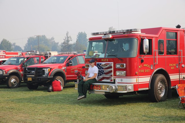 A firefighter rests on the bumper of a truck at a fire camp in Hood River.