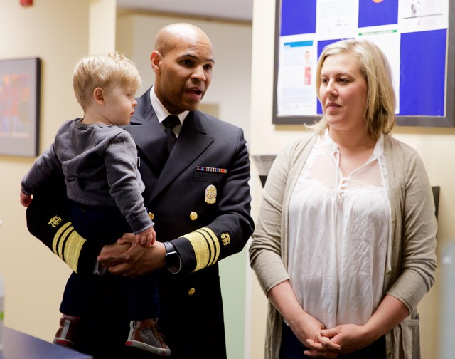 Surgeon General Jerome Adams holds 15-month-old Everett Banse-Fay. His mother, Cerise Wilson, was initially hesitant to fully vaccinate him after talking to friends and going on-line to find information.