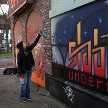 "Bree Judah, paint location foreman for Grimm, defaces the sign she and a coworker painted a day earlier to blend it into the other wall graffiti. ""You can't get attached to it,"" she says."