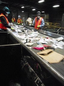 Workers pull out trash from recyclable material on conveyor belts at the Far West Fibers recycling facility in Northeast Portland.
