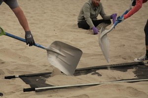 Volunteers scoop sand onto microplastics filtration systems at Cannon Beach.