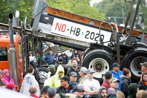 A flatbed truck rides by as a crowd rallies at the Capitol in Salem to protest House Bill 2020.