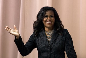 """Former first lady Michelle Obama waves to the audience during a stop on her book tour for """"Becoming,"""" in Washington, Sunday, Nov. 25, 2018."""