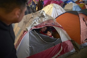 In this March 5, 2019, image, Ruth Aracely Monroy, center, looks out of the family's tent alongside her 10-month-old son, Joshua, as her husband, Juan Carlos Perla, left, passes inside a shelter for migrants in Tijuana, Mexico.