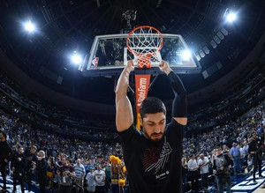 Portland Trail Blazers center Enes Kanter hangs on the net before the first half of Game 7 of an NBA basketball second-round playoff series against the Denver Nuggets Sunday, May 12, 2019, in Denver.