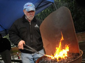 Fred Martin places a piece of gun metal into the hot coals.