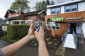 In this 2017 photo, Hush co-owner David Gor photographs the new sign going up on the side of the recreational marijuana shop he and a group of partners are opening in Eugene, Ore.